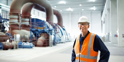 Close up picture of an engineer in front of a turbine in a power plant