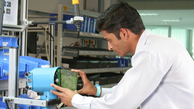 production competence, man inserts printed circuit board